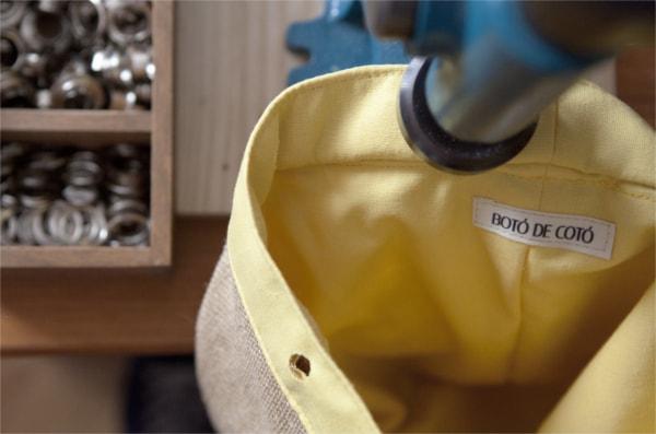 Colocar ollaos a mochila en el taller de boto de coto