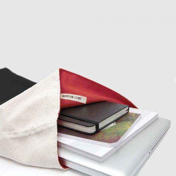 mochila enrollable de color beige y negro con forro interior rojo